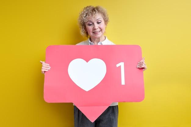 Knappe bejaarde vrouw geniet ervan actief te zijn in internetbloggen, hart als teken in handen te houden