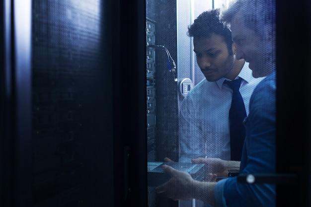Knappe bekwame mannelijke technicus die samen in de buurt van de gegevensserver staat en een bladeserver installeert tijdens het werken in de serverruimte