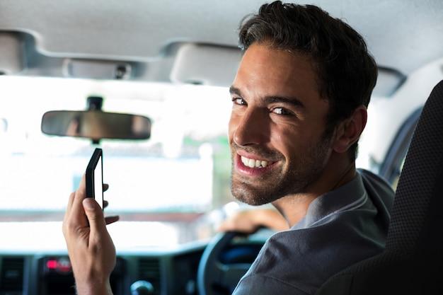 Knappe bestuurder die telefoon gebruikt