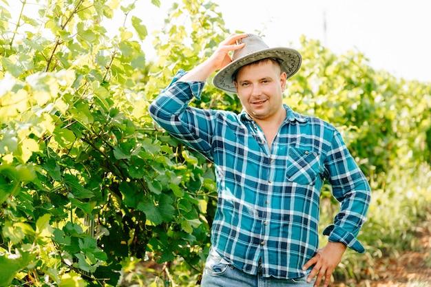 Knappe blanke boer man kijkt naar de camera en glimlacht knappe wijnmaker is in de wijngaard met...