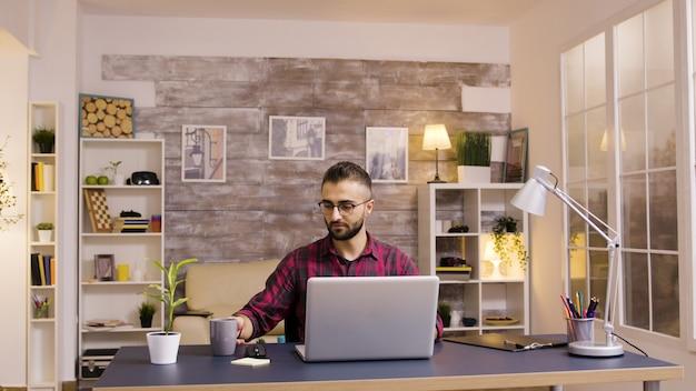 Knappe blanke freelancer die op laptop werkt vanuit kantoor aan huis.