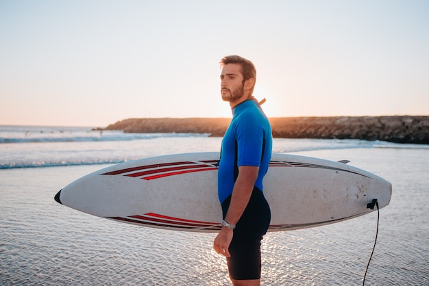 Knappe blanke jongen die het bord grijpt om te surfen terwijl hij naar de zijkant kijkt aan de kust van portugal