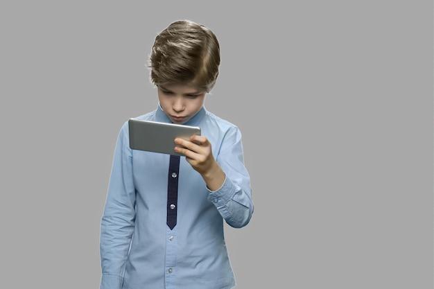 Knappe blanke jongen met behulp van smartphone. weinig jongen die celtelefoon op grijze achtergrond bekijkt. vrije tijd, kinderen, technologie, internetverslaving en mensenconcept.