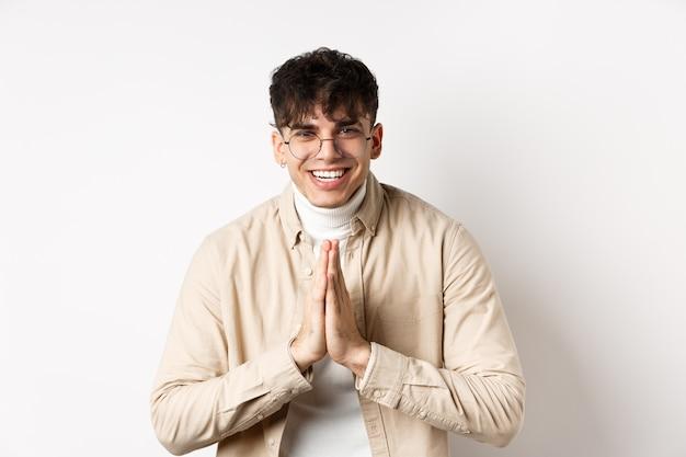 Knappe blanke man bedankt, buigt met namaste-gebaar, kijkt dankbaar en lacht naar de camera, staande op een witte muur.