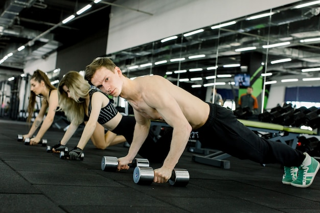 Knappe blanke man en twee mooie vrouwen doen plank oefening met zware halters in de sportschool