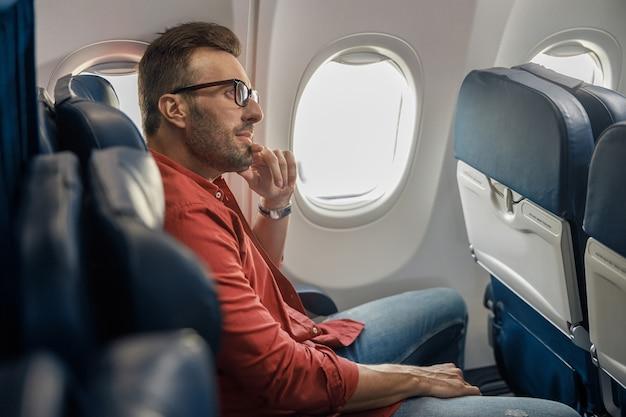 Knappe blanke man in vrijetijdskleding en een bril die wegkijkt, zittend in het vliegtuig bij het raam. ontspan, reizen, vakantie, transportconcept