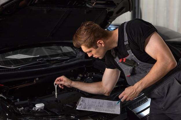 Knappe blanke man maakt aantekeningen tijdens het repareren van de motorkap van de auto