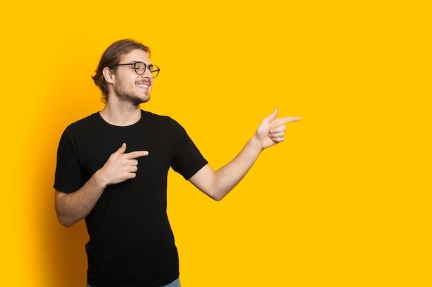 Knappe blanke man met baard en bril die naar de vrije ruimte op een gele muur wijst