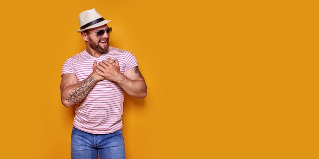 Knappe blanke man met baard met een casual gestreept t-shirt glimlachend met handen op de borst met gr...