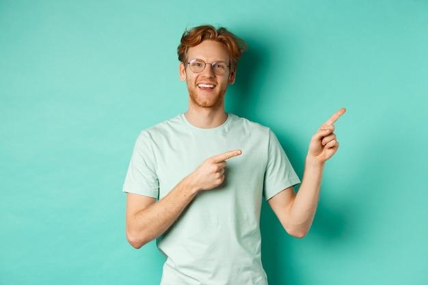Knappe blanke man met gemberhaar, bril en t-shirt, wijzende vingers naar rechts en vrolijk lachend, reclame tonend, staande over turkooizen achtergrond.