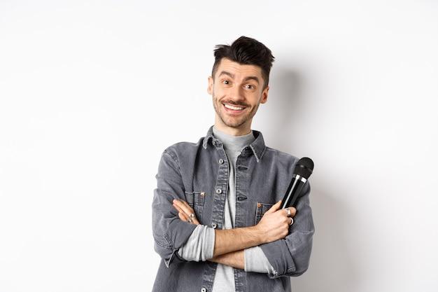 Knappe blanke man met snor kruis armen op de borst, microfoon vasthouden en glimlachen naar de camera, optreden op het podium met microfoon, staande tegen een witte achtergrond.