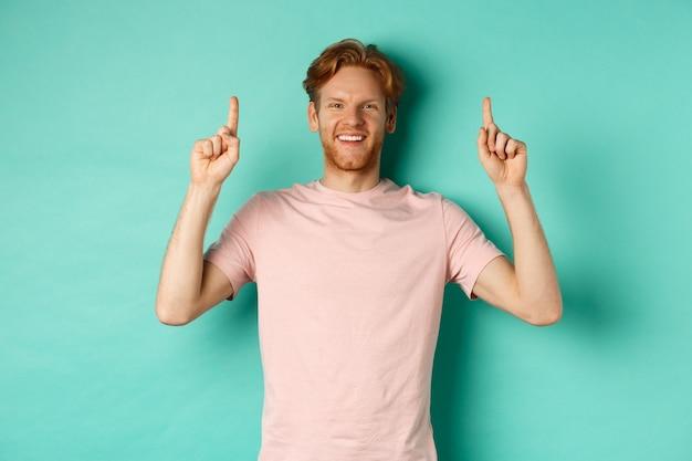 Knappe blanke man met witte tanden, gelukkig lachend en met de vingers omhoog, promo-aanbieding tonend, staande over muntachtergrond