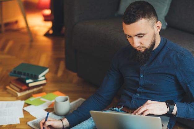Knappe blanke ondernemer met grote baard werkt op zijn laptop terwijl hij iets schrijft en koffie drinkt