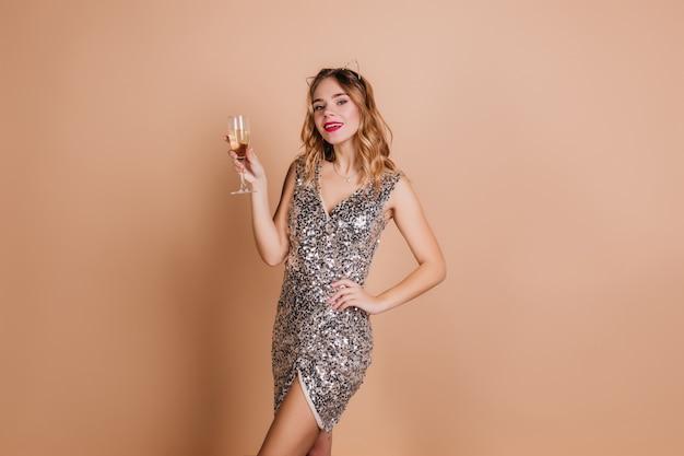 Knappe blanke vrouw in stijlvolle kleding staande in zelfverzekerde pose met wijnglas op lichte muur
