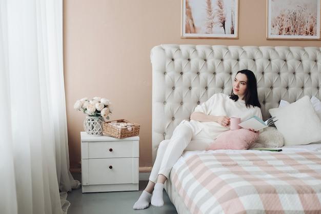 Knappe blanke vrouw ligt op het grote lichte bed en denkt na over haar toekomstplannen