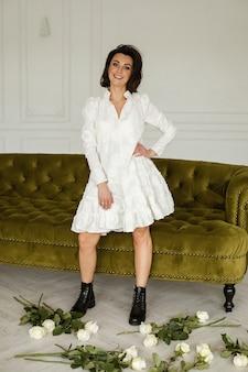 Knappe blanke vrouw met donker haar in witte jurk en zwarte laarzen staat in de buurt van de witte rozen