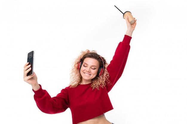Knappe blanke vrouw met krullend blond haar drinkt koffie en doet selfie