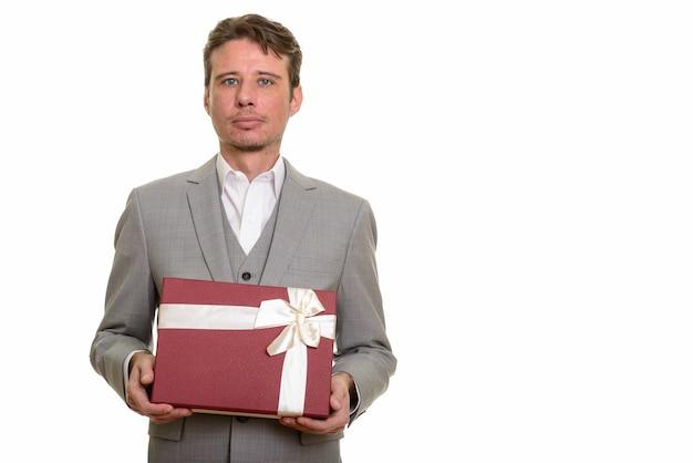 Knappe blanke zakenman bedrijf geschenkdoos klaar voor valent