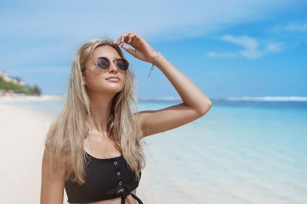 Knappe blonde gelooide vrouw die zich voordeed op zandstrand in de buurt van blauwe oceaan