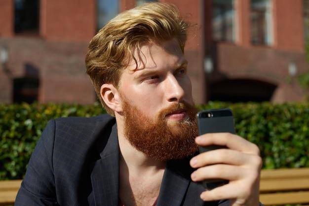 Knappe blonde hipster dagdromen met telefoon in de hand