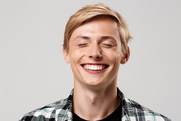 Knappe blonde jonge man met casual geruite overhemd lachend met de ogen gesloten op grijze muur