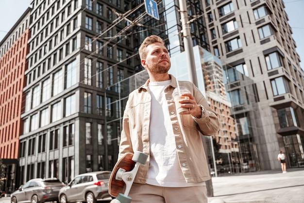 Knappe blonde jongeman skateboarder met longboard en kopje koffie afhaalmaaltijden ziet er serieus gefocust uit terwijl hij de weg oversteekt op de achtergrond van een stedelijk gebouw. draagt een casual denim outfit.