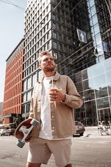 Knappe blonde jongeman skateboarder met longboard op schouder en kopje koffie afhaalmaaltijden ziet er serieus gefocust uit terwijl hij de weg oversteekt op de achtergrond van een stedelijk gebouw. draagt een casual denim outfit.