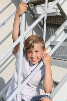 Knappe blonde jongen in een wit overhemd glimlachend staande op een witte trap in de zomer. hoge kwaliteit foto