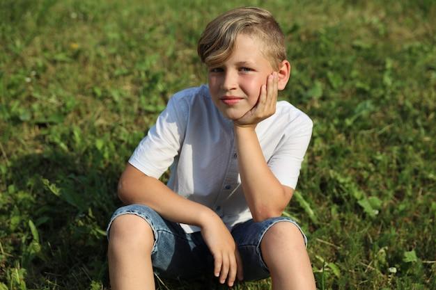 Knappe blonde jongen zittend op het gras in de zomer in het park. hoge kwaliteit foto