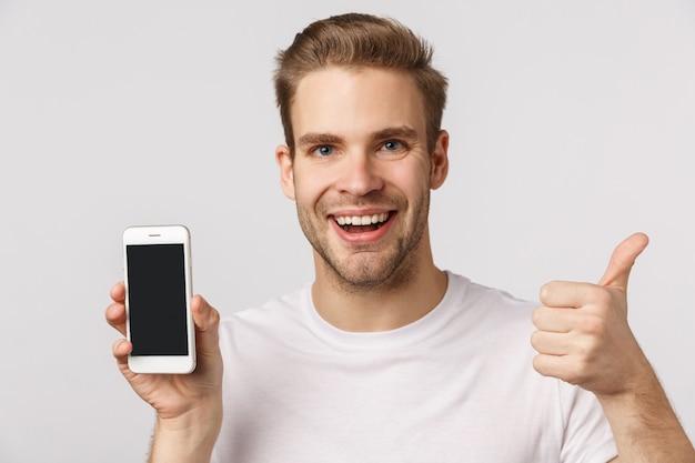 Knappe blonde kerel die met blauwe ogen smartphone houden