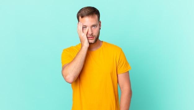 Knappe blonde man die zich verveeld, gefrustreerd en slaperig voelt na een vermoeiende