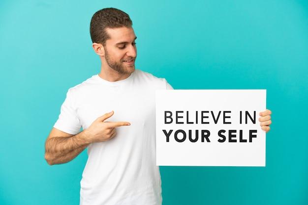 Knappe blonde man isoleerde blauwe achtergrond met een bordje met de tekst geloof in jezelf en wees erop
