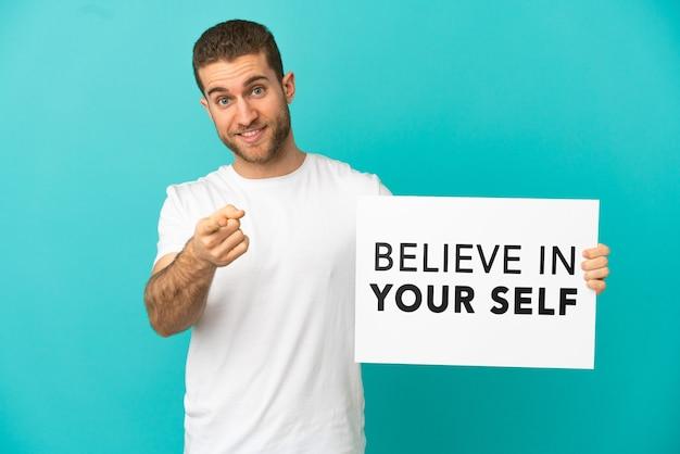 Knappe blonde man isoleerde blauwe achtergrond met een bordje met tekst believe in your self en wijzend naar voren