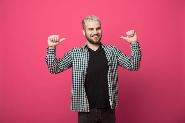 Knappe blonde man met baard wijst naar zichzelf en lacht naar de camera op een rode studiomuur