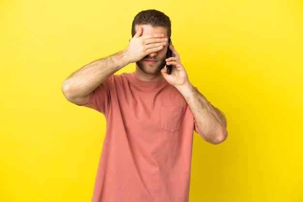 Knappe blonde man met behulp van mobiele telefoon over geïsoleerde achtergrond die ogen bedekken door handen. ik wil niets zien