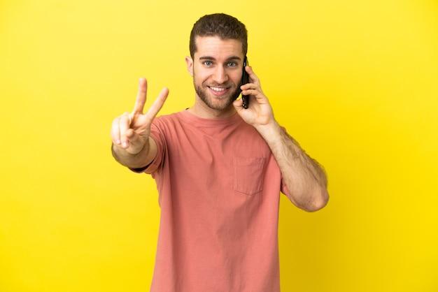 Knappe blonde man met behulp van mobiele telefoon over geïsoleerde achtergrond glimlachend en overwinningsteken tonen