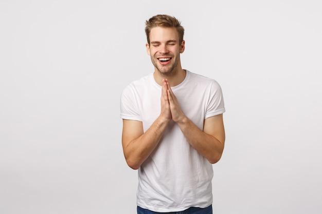 Knappe blonde man met blauwe ogen en wit t-shirt in de hoop succes te behalen