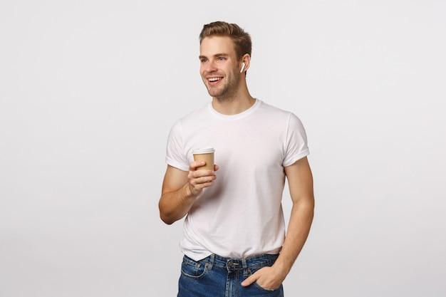 Knappe blonde man met blauwe ogen en witte t-shirt papier koffiemok houden