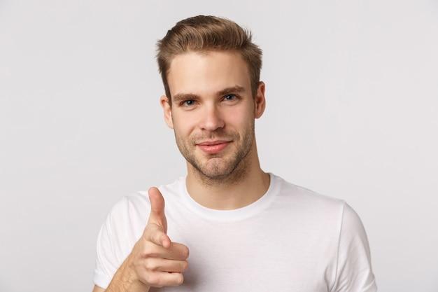 Knappe blonde man met blauwe ogen en witte t-shirt wijzen