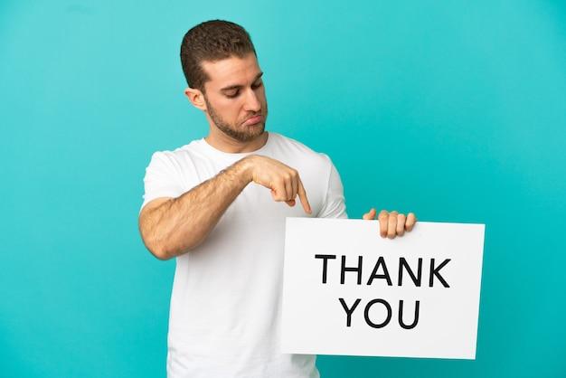 Knappe blonde man over geïsoleerd met een bordje met de tekst bedankt en erop wijzend