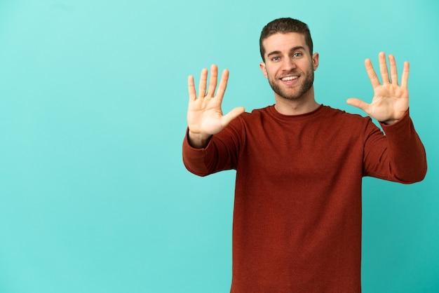 Knappe blonde man over geïsoleerde blauwe achtergrond die tien telt met vingers