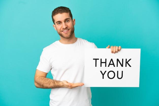 Knappe blonde man over geïsoleerde blauwe achtergrond met een bordje met de tekst dank u en erop wijzend