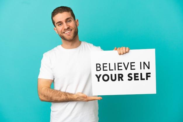 Knappe blonde man over geïsoleerde blauwe achtergrond met een bordje met de tekst geloof in jezelf en erop wijzend