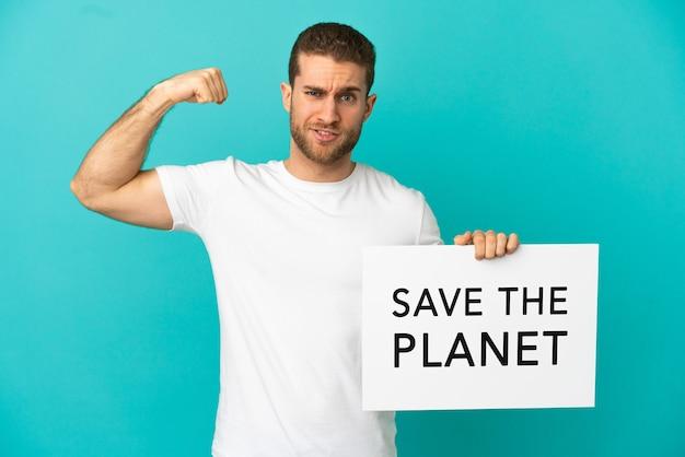 Knappe blonde man over geïsoleerde blauwe achtergrond met een bordje met de tekst save the planet en een sterk gebaar doen
