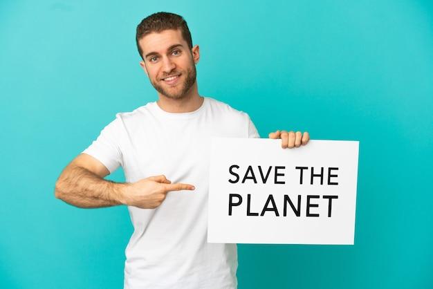 Knappe blonde man over geïsoleerde blauwe achtergrond met een bordje met de tekst save the planet en erop wijzend