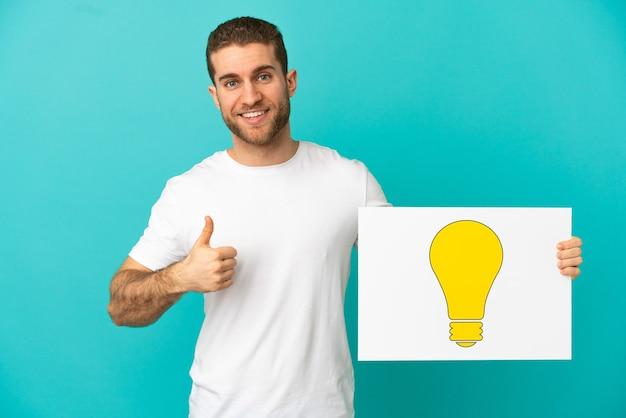Knappe blonde man over geïsoleerde blauwe achtergrond met een bordje met lamppictogram met duim omhoog