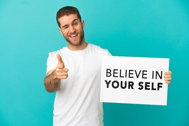 Knappe blonde man over geïsoleerde blauwe achtergrond met een bordje met tekst believe in your self en naar voren wijzend
