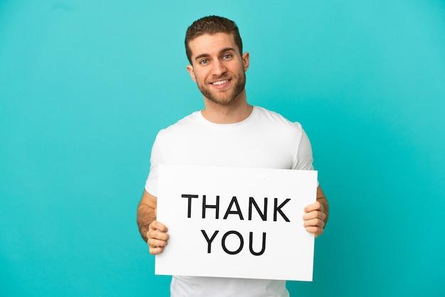 Knappe blonde man over geïsoleerde blauwe achtergrond met een bordje met tekst dank u met gelukkige uitdrukking