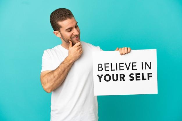 Knappe blonde man over geïsoleerde blauwe achtergrond met een bordje met tekst geloof in je zelf en denken