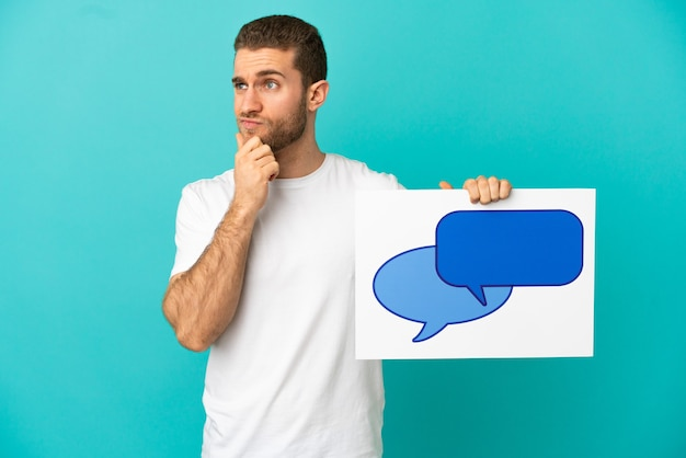 Knappe blonde man over geïsoleerde blauwe achtergrond met een bordje met tekstballonpictogram en denken